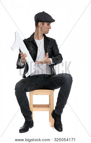 handsome casual man wearing a black leather jacket and hat sitting and presenting his number one to a side cocky against white studio background