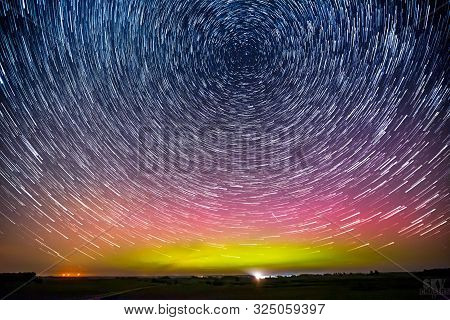 Star Trails Around The Polar Star Or Polaris And Green Glowing Display Of Northern Lights Or Aurora