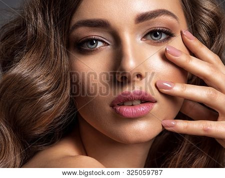 Beautiful woman with natural color of nails. Beautiful face of an attractive model with fashion makeup. Woman with beauty long curly brown  hair. Closeup portrait of a caucasian female. Stunning girl.
