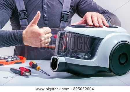 Repairman Repairing Of Vacuum Cleaner. Small Business.