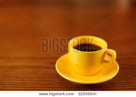 Yellow Coffee Cup on Wooden Table