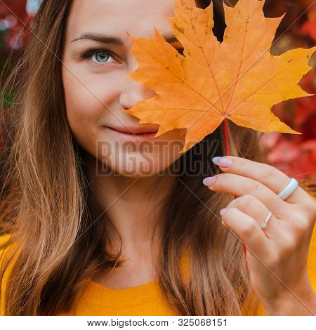 Beautiful Young Woman Covering Her Face With A Yellow Autumn Leaf, Smiling Against The Reddened Foli