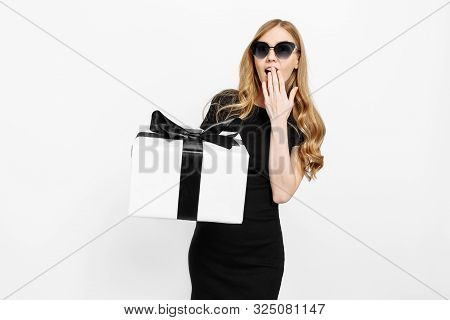 poster of Beautiful young girl in black dress holding Black Friday gifts. A woman on a white background holds a gift box with a black ribbon. Gifts, shopping, Black Friday