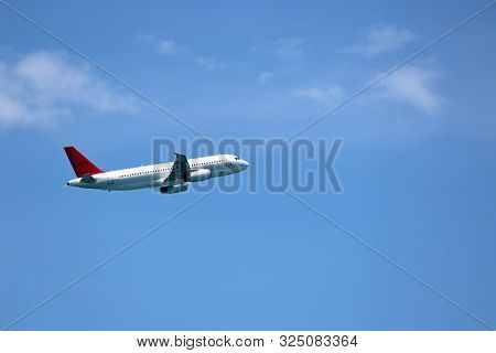 Airplane Flying In The Blue Sky On Background Of White Clouds, Side View. Two-engine Commercial Plan