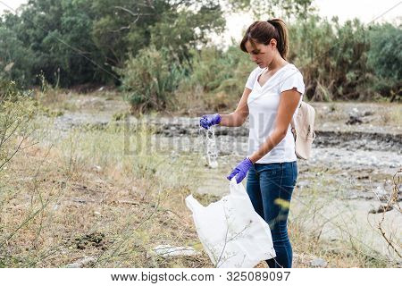 Stock Photo Of A Girl In A White T-shirt And Jeans With Blue Gloves Collecting Plastic In A Forest T