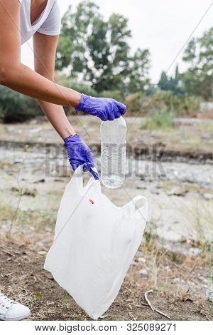 Stock Photo Of The Hands Of A Girl With Blue Gloves Picking Up A Plastic Bottle And Putting It In A