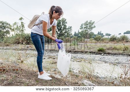 Stock Photo Of A Girl In A White T-shirt And Jeans With Blue Gloves Putting A Plastic Bottle In A Ba
