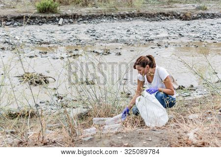 Stock Photo Of A Girl With Blue Gloves Crouched On The Bank Of The River Collecting Plastic Bottles.