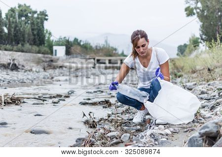 Stock Photo Of A Woman With Blue Gloves Crouched On The Bank Of The River Putting A Plastic Bottle I