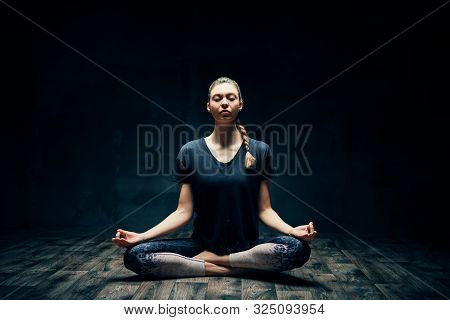 Young Attractive Woman Practicing Yoga Sitting In Lotus Pose And Meditating In Dark Room. Ardha Padm