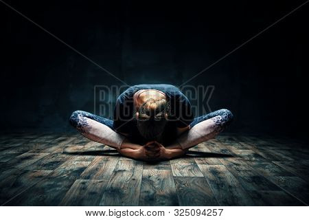 Young Woman Practicing Yoga Doing Reclined Goddess Pose Asana In Dark Room. Supta Baddha Konasana. W