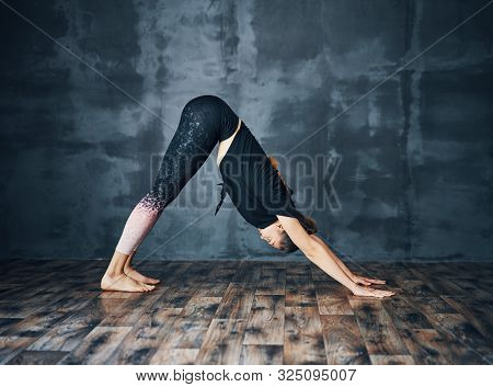 Young Attractive Woman Practicing Yoga Standing In Downward Facing Dog Asana Adho Mukha Svanasana Po