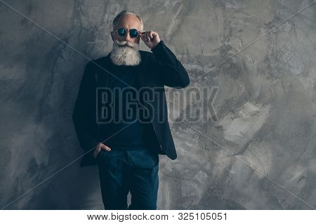 Portrait Of Classy Harsh Masculine Man Touching His Specs Looking Wearing Black Coat Jacket Trousers