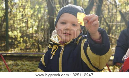 Autumn Time. Little Smiling Child With Yeallow Leaf Dressed In Black-yeallow Jacket In The Kindergar