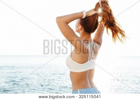 Picture of young redhead sports woman outdoors at the beach in the morning listening music with wireless bluetooth earphones correct her ponytail.