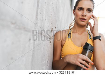 Image of feminine woman with earpods holding water bottle over concrete wall outdoors