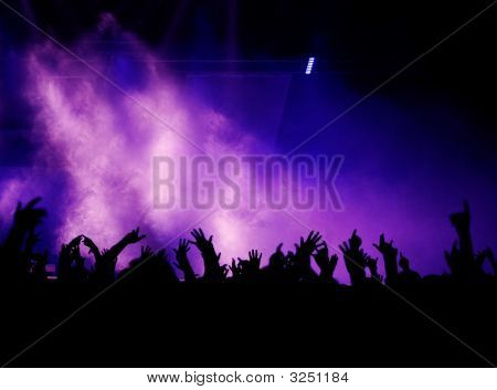 Crowd raising arms hands and fingers at a pop concert; silhouette of audience nice fog and lights in magenta and blue in the background poster