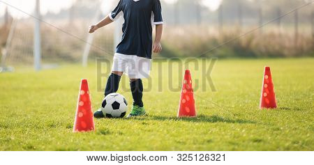 Soccer Player Dribbling Through Cones In The Ground On A Sunny. Young Boy Soccer (european Football)