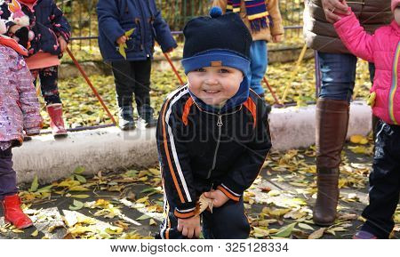Autumn Time. Little Smiling Child With Yeallow Leaf Dressed In Black Jacket And Hat In The Kindergar