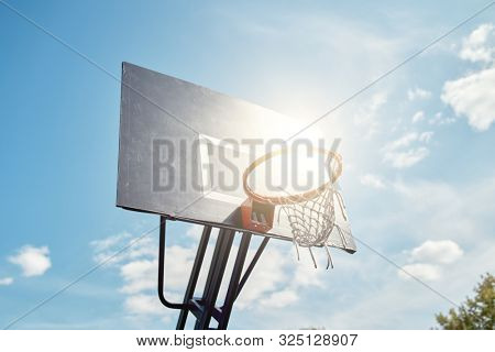Photo of basketball hoop against blue, cloudy sky on summer day.