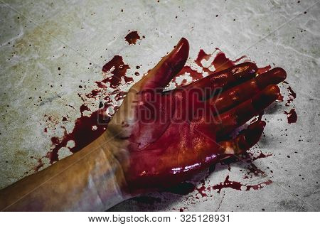 Hand Of A Killed Person In A Bloody Puddle. Concept Of A Victim Of Murder