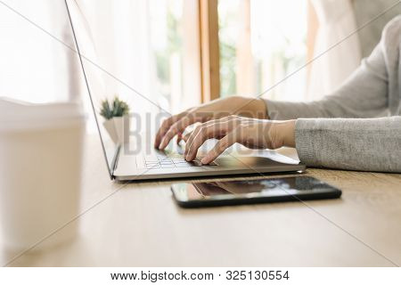 Business Woman Hand Typing Laptop Computer On Wooden Table