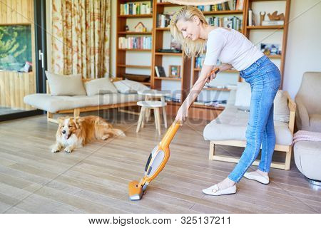 Housewife as a cleaner with vacuum cleaner at the parquet floor vacuuming