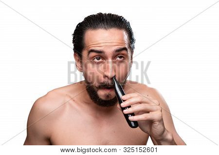 Handsome Bearded Man With Mustache Uses Power Trimmer To Trim Hair In The Nose Standning Bare Isolat