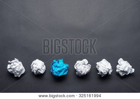 Crumpled Blue Paper Ball Among White Balls On Black Background. Dissimilar Solution Of Problem. Thin