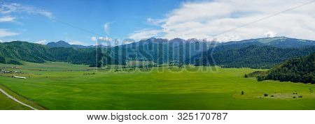 Mountain View With Sibirian Altai Mountains And Green Grass Field, Small Forest And Village, Blue Sk