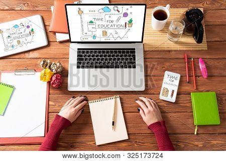 Time For Education Concept With Office Workspace. Flat Lay Wooden Desk With Laptop, Woman Hands And