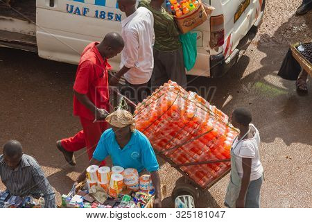 Kampala, Uganda - October 03, 2012.  An African Man Moves Cases Of Soda Pop Across The Taxi Park In
