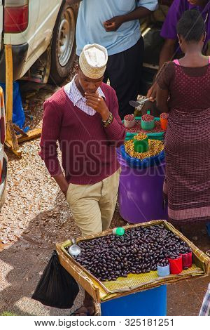 Kampala, Uganda - October 03, 2012.  A Young Man Ponders By His Tray Of Beans For Sale At The Taxi P