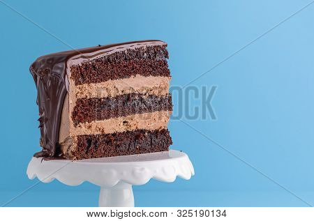 Appetizing Slice Of Chocolate Layered Birthday Cake Close-up On Blue Background. Homemade Cocoa New