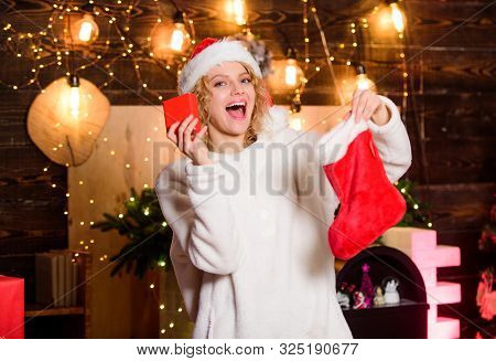 Stockings Filled With Many Fun Things, Called Christmas Stocking Stuffers. Woman Hold Red Stocking.