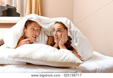 Married couple lyining in bed under duvet. Affectionate couple in intimate time.