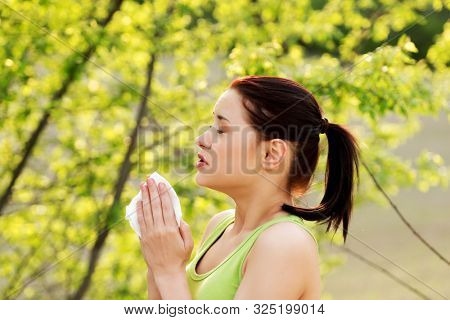 Side view of woman sneezing in tissue because of allergy on pollen, outdoor.