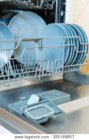 Open Dishwasher With Dishes And Eco Green Dishwasher Tablet. Vertical. Eco Detergent For Dishwasher.