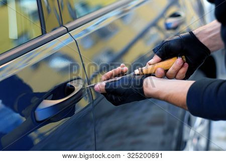 Closeup Male Hands In Black Gloves Is Trying To Open, Break Into Automobile Without Signaling Alarm.