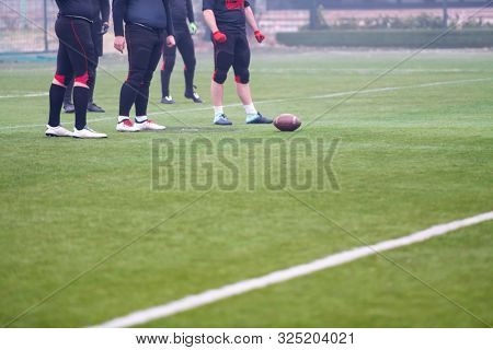 group of young professional american football players practicing football kickoff during training on the stadium field with focus on the legs
