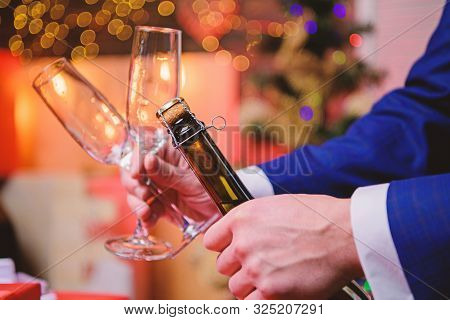 Male Hands Opening Champagne Bottle On Christmas Decorations Background. Open Champagne And Celebrat