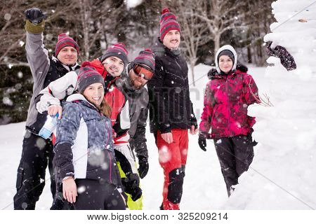 group portrait of young happy business people after a competition posing with finished snowman while enjoying snowy winter day with snowflakes around them during a team building in the mountain forest