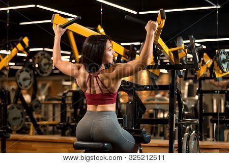 Sexy Fitness Brunette Girl Is Sitting And Doing Shoulder Exercises In Trainer