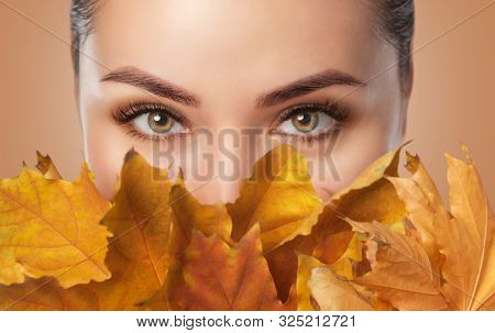 Beautiful Woman With Long Eyelashes And With Beautiful Smokey Eyes Makeup Holds Yellow Leaves Near T