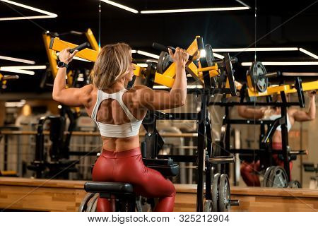Blonde Bodybuilder Woman Is Sitting And Doing Shoulder Exercises In Trainer
