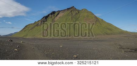 Panoramic view on green Hattafell mountain in Volcanic landscape with resting tourist. Laugavegur trek in area of Fjallabak Nature Reserve in Highlands region of Iceland poster