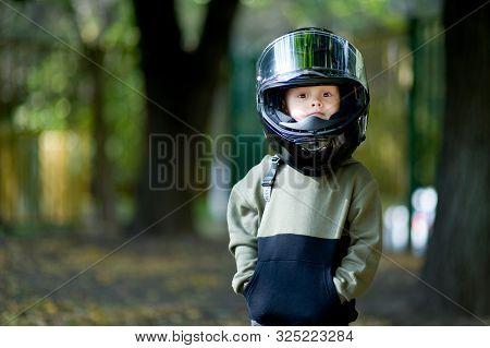 Funny Kid With A Big Motorcycle Helmet On His Head. Helmet Boy