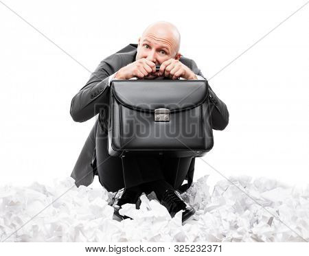 Business problems and failure at work concept - unhappy scared or terrified businessman in depression hand holding briefcase sitting down floor on crumpled torn paper document heap white isolated