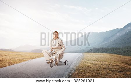 Beautiful caucasian woman riding kids bicycle on asphalt road. Young employee in white business suit biking outdoor. Professional career start. Beginner level concept with female bicyclist. poster