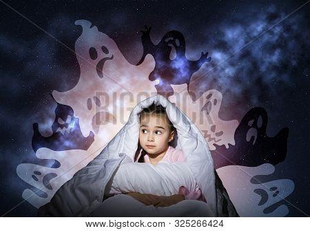 Scared Girl Hiding Under Blanket. Startled Kid Sitting In Bed On Background Night Sky. Child Afraid